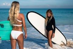 Mujer joven hermosa en bikini con el tablero de resaca en la playa de la isla tropical Foto de archivo libre de regalías