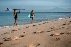 Mujer joven hermosa en bikini con el tablero de resaca en la playa de la isla tropical Imagen de archivo libre de regalías