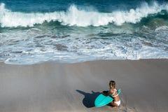 Mujer joven hermosa en bikini con el tablero de resaca en la playa de la isla tropical Foto de archivo