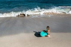 Mujer joven hermosa en bikini con el tablero de resaca en la playa de la isla tropical Imágenes de archivo libres de regalías
