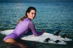 Mujer joven hermosa en bikini con el tablero de resaca en la playa de la isla tropical Fotografía de archivo libre de regalías