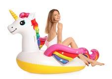 Mujer joven hermosa en bikini elegante con el anillo inflable del unicornio en blanco fotos de archivo