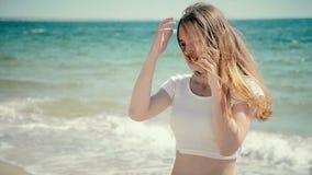 Mujer joven hermosa en bikini que habla el teléfono elegante en la playa del mar Verano soleado por el mar almacen de video