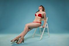 Mujer joven hermosa en bikini rojo con el cóctel en fondo azul fotografía de archivo libre de regalías