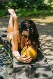 mujer joven hermosa en bikini y gafas de sol que bebe el cóctel tropical foto de archivo