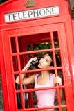 Mujer joven hermosa en cabina de teléfono Imagen de archivo