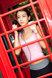 Mujer joven hermosa en cabina de teléfono Fotos de archivo
