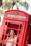 Mujer joven hermosa en cabina de teléfono Imagen de archivo libre de regalías