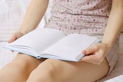Mujer joven hermosa en cama que lee un libro Fotografía de archivo libre de regalías