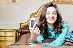 Mujer joven hermosa en cama que sonríe tomando un selfie Imagen de archivo