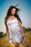 Mujer joven hermosa en campo de flores salvajes en fondo del cielo azul Retrato de la muchacha morena atractiva con el pelo largo Imágenes de archivo libres de regalías