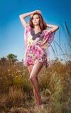 Mujer joven hermosa en campo de flores salvajes en fondo del cielo azul Retrato de la muchacha roja atractiva del pelo con el pel Imagenes de archivo