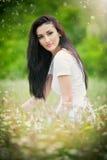 Mujer joven hermosa en campo de flores salvajes Retrato de la muchacha morena atractiva con el pelo largo que se relaja en la nat Foto de archivo