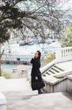Mujer joven hermosa en capa de lana oscura en la calle en el tiempo de primavera Flores de las flores de la almendra, capa de mod fotografía de archivo libre de regalías