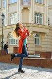 Mujer joven hermosa en capa que camina abajo de la calle Imágenes de archivo libres de regalías