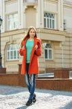 Mujer joven hermosa en capa que camina abajo de la calle Fotos de archivo libres de regalías