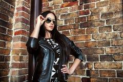 Mujer joven hermosa en chaqueta de cuero y gafas de sol negras Imagen de archivo libre de regalías