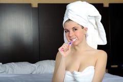 Mujer joven hermosa en dientes que aplican con brocha de la toalla Foto de archivo libre de regalías