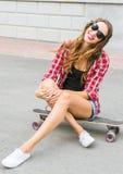 Mujer joven hermosa en el asiento en patín, forma de vida de las gafas de sol de la moda de la calle Imagen de archivo
