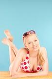 Mujer joven hermosa en el bikini que miente en una playa imagen de archivo libre de regalías
