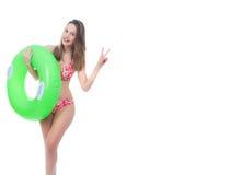 Mujer joven hermosa en el bikini que presenta con un anillo de goma verde grande Foto de archivo libre de regalías