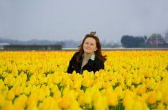 Mujer joven hermosa en el campo de tulipanes amarillos Fotos de archivo