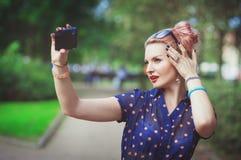Mujer joven hermosa en el estilo de los años 50 que toma la imagen de sí misma Imagen de archivo
