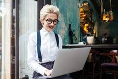 Mujer joven hermosa en el funcionamiento de vidrios en el ordenador portátil y la sonrisa Fotografía de archivo