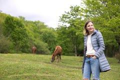 Mujer joven hermosa en el parque con los caballos tiempo de la primavera imagenes de archivo
