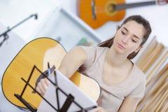 Mujer joven hermosa en el sofá con la guitarra Imagenes de archivo