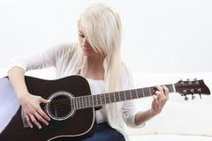 Mujer joven hermosa en el sofá con una guitarra Fotos de archivo