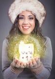 Mujer joven hermosa en el sombrero blanco que sostiene la casa mágica imagen de archivo libre de regalías