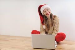 Mujer joven hermosa en el sombrero de santa que busca los presentes en línea para imagen de archivo libre de regalías