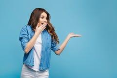 Mujer joven hermosa en el suéter amarillo que presenta en fondo azul Mujer atractiva que señala los fingeres a la derecha con Imagenes de archivo