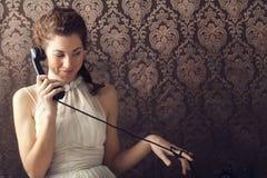 Mujer joven hermosa en el teléfono en sala de estar imagen de archivo