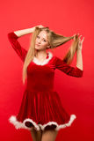 Mujer joven hermosa en el traje de Papá Noel que juega con un filamento de su pelo sedoso largo, mirando la cámara en fondo rojo Fotos de archivo
