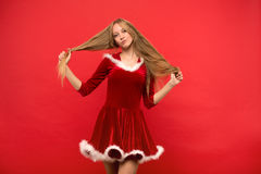 Mujer joven hermosa en el traje de Papá Noel que juega con un filamento de su pelo sedoso largo, mirando la cámara en fondo rojo Fotografía de archivo