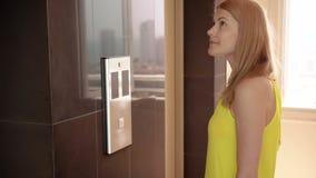 Mujer joven hermosa en el vestido amarillo que espera un elevador Empujar un botón que llama una elevación metrajes
