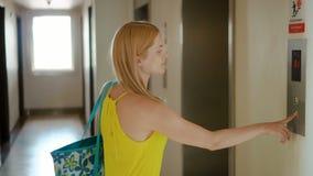 Mujer joven hermosa en el vestido amarillo que espera un elevador Empujar un botón que llama una elevación almacen de metraje de vídeo