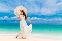 Mujer joven hermosa en el vestido blanco con el paraguas en un tropical Foto de archivo libre de regalías