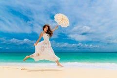 Mujer joven hermosa en el vestido blanco con el paraguas en un tropical Fotos de archivo libres de regalías