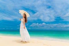Mujer joven hermosa en el vestido blanco con el paraguas en una playa tropical Imagen de archivo libre de regalías