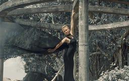 Mujer joven hermosa en el vestido de noche negro que sostiene la tela negra en el viento imagen de archivo libre de regalías