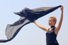 Mujer joven hermosa en el vestido de noche negro que sostiene la tela negra en el viento en la playa imágenes de archivo libres de regalías