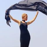 Mujer joven hermosa en el vestido de noche negro que sostiene la tela negra en el viento en la playa imagen de archivo