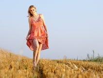 Mujer joven hermosa en el vestido del verano que se coloca en campo Foto de archivo