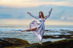 Mujer joven hermosa en el vestido largo que agita en la estancia del viento en la playa del océano en la roca en puesta del sol e imagen de archivo libre de regalías
