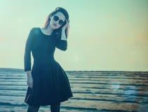 Mujer joven hermosa en el vestido negro que se coloca en la playa Fotos de archivo libres de regalías