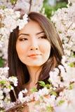 Mujer joven hermosa en fondo de la flor Foto de archivo libre de regalías