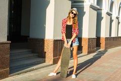 Mujer joven hermosa en gafas de sol con el patín, forma de vida de la moda de la calle Imágenes de archivo libres de regalías